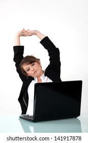 Businesswoman sat at desk stretching