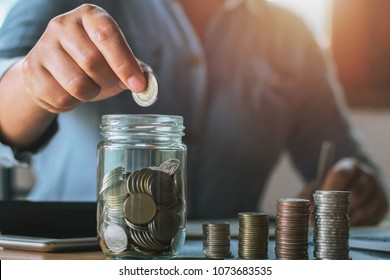 businesswoman saving money by hand puting coins in jug glass. concept  finance and accounting