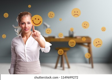 businesswoman is selecting a good mood smiley out of many sad ones