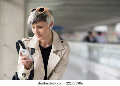 Businesswoman sending message with mobile phone at Charles de Gaulle airport, Paris.