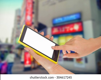 Businesswoman sending messages with her mobile phone, building Background