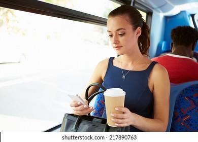 Businesswoman Sending Text Message On Bus