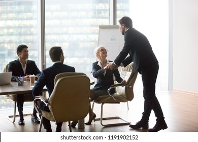 Businesswoman shaking hand of male coach mentor thanking for successful presentation at company meeting, presenter handshaking female boss making good first impression before lecture or seminar