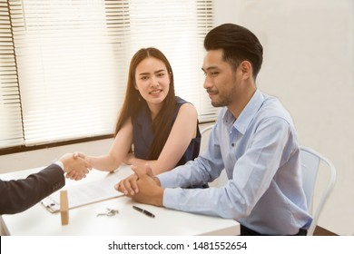 Businesswoman shaking hand with a young couple in office. Bank agent and his client shaking hands in conference room. Happy smiling couple seal a deal with their personal financial adviser.