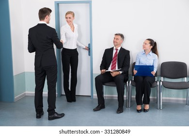 Businesswoman Shaking Hands With Man In Front Of People Waiting For Job Interview In Office