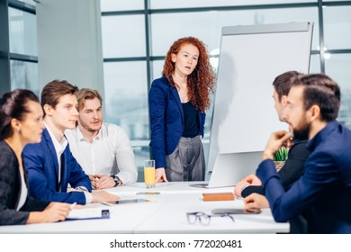 Businesswoman showing project on flipchart while giving presentation to colleagues in office
