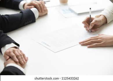 Businesswoman signing business document at group meeting, client customer puts signature on contract agreement buying services, taking bank loan, making legal partnership deal concept, close up view