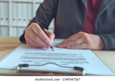 Businesswoman signing contract and business partnership agreement at office desk