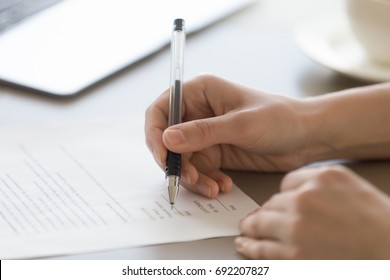 Businesswoman signing document concept, focus on female hand holding pen, putting signature on legal document, giving permission by authorization, subscribing contract, binding agreement, close up