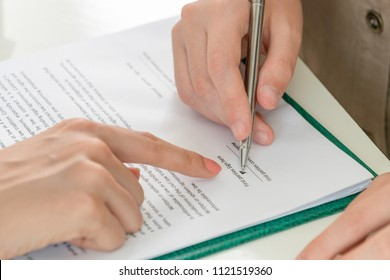 Businesswoman signs agreement contract with another businesswoman at the office. Close up shot at the woman's hand. Concept of job application and legal activities of lawyer.
