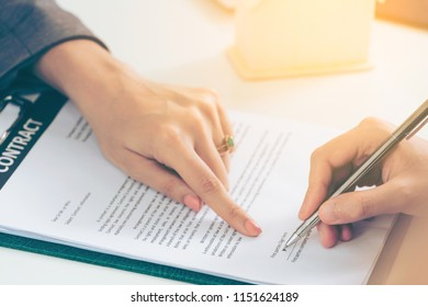 Businesswoman signs agreement contract with another businesswoman at the office. Close up shot at the woman's hand. Concept of business partnership and legal activities of lawyer.