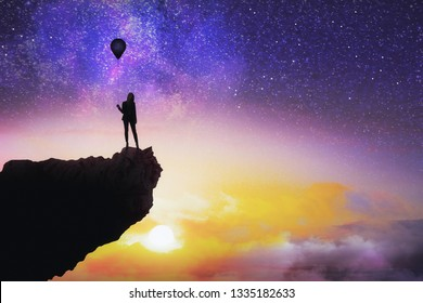 Businesswoman silhouette with balloon on cliff standing on beautiful starry sky background with sunset. Freedom and success concept
