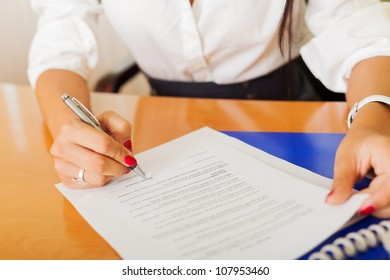 businesswoman singing contract in office
