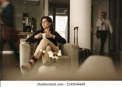 Businesswoman sitting at the airport lounge, waiting for the flight. Thoughtful woman sitting on sofa with coffee at airport waiting area.