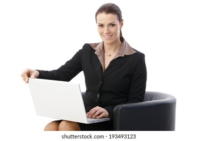 Businesswoman sitting in armchair with laptop computer, smiling at camera, isolated on white.