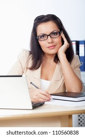 businesswoman sitting behind the desk looking at camera