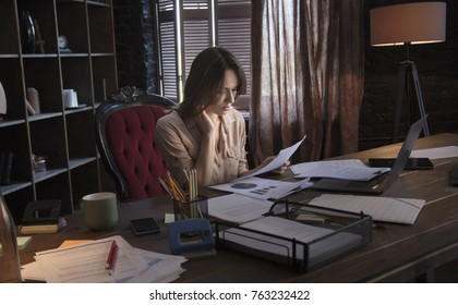 Businesswoman sitting in chair behind table with holding in hand documents