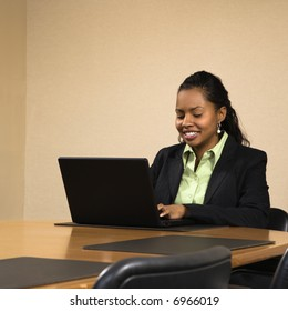Businesswoman sitting at conference table smiling and typing on laptop computer.