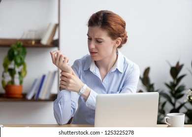 Businesswoman sitting at desk in office touch wrist feels pain. Unhealthy upset female having carpal tunnel syndrome because of active and long-term use of the keyboard and mouse in the wrong posture