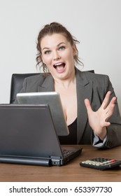 businesswoman sitting at desk working on a tablet computer