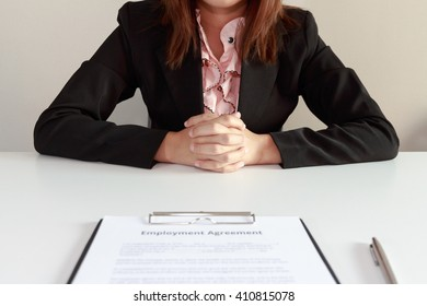 Businesswoman sitting with employment agreement in front of her concept
