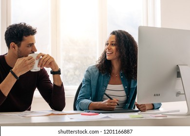 Businesswoman sitting in front of a computer writing on a digital writing pad talking to her colleague. Businessman discussing work with female colleague at office while drinking coffee.