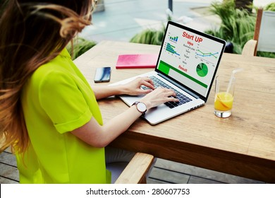 Businesswoman sitting front laptop computer with financial information as graphics and charts on screen, young female entrepreneur work with statistics data and analyzing performance on her notebook