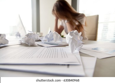 Businesswoman sitting with head in hands at desk covered crumpled papers. Office worker tired of too much difficult unproductive work. Stressed female entrepreneur has no idea what to do with problem