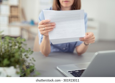 Businesswoman sitting at her desk in front of a laptop computer reading a folded document, close up of her hands and the paperwork