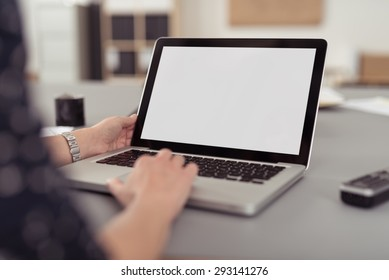 Businesswoman sitting at her desk navigating the internet on a laptop computer using the trackpad, over the shoulder view of the blank screen