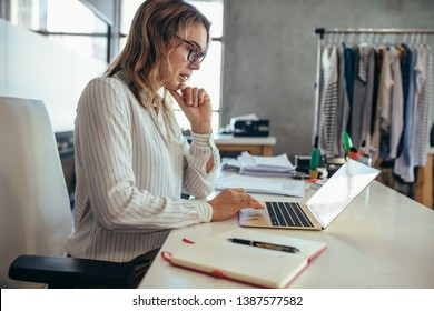 Businesswoman sitting at her desk and working on laptop. Dropshipping business owner looking for new orders on her laptop.