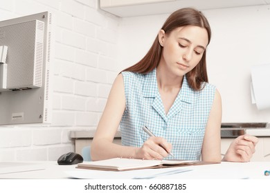 Businesswoman is sitting at his desk and writing in a notebook.