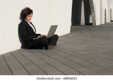 Businesswoman sitting with a laptop at the wall outdoors