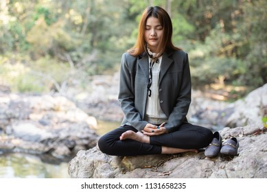 Businesswoman sitting meditation in lotus pose on nature environment for benefits pond water background.