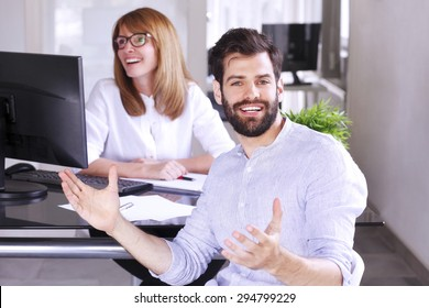 Businesswoman sitting at office desk and interviewing young professional man. Middle age professional woman sitting in front of computer and making successful business deal with young businessman.