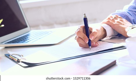 Businesswoman sitting at office desk signing a contract or making notes.