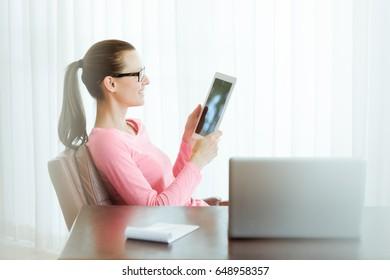 Businesswoman sitting in office using a smart tablet.