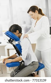 Businesswoman sitting on massage chair, getting back massage.?