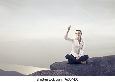 Businesswoman sitting on a rock over a lake and writing
