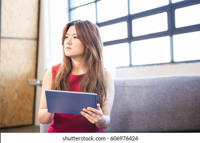 Businesswoman sitting on sofa and using digital tablet in office
