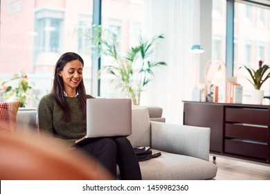 Businesswoman Sitting On Sofa Working On Laptop At Desk In Shared Workspace Office