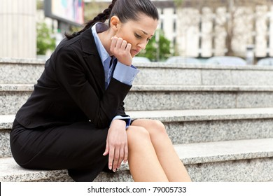 businesswoman sitting on the stairs of the company troubled after getting the news he was fired