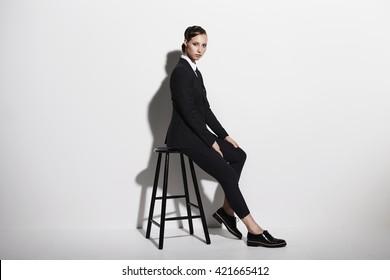 Businesswoman sitting on stool, portrait