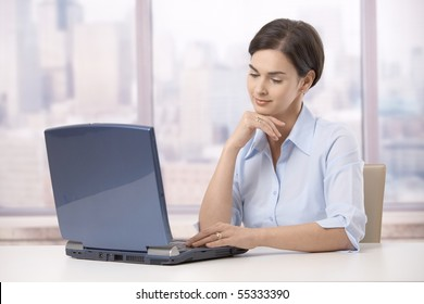 Businesswoman sitting at skyscraper office, working on laptop computer.?