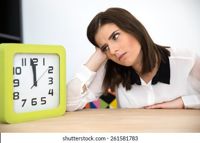 Businesswoman sitting at the table with clock. Waiting for break