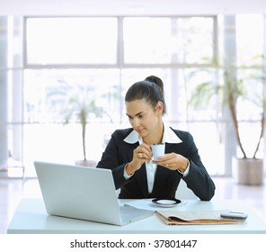 Businesswoman sitting at table in office lobby, drinking coffee and using laptop computer.