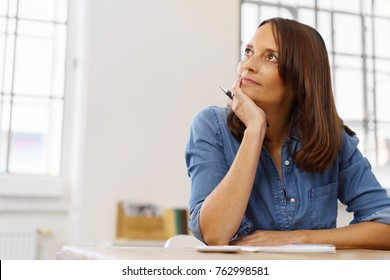 Businesswoman sitting thinking as she works on paperwork resting her chin on her hand and staring off to the side