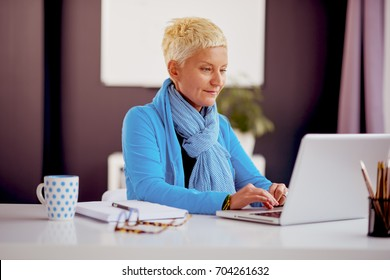 Businesswoman sitting and using laptop computer in modern office