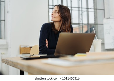 Businesswoman sitting watching to the side with a smile while leaning on her desk with a laptop computer in a low angle view