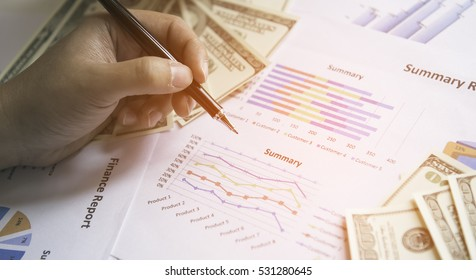businesswoman sitting working at her desk in the office checking and analysing a report. Accounting,Pen in hand on Graph background